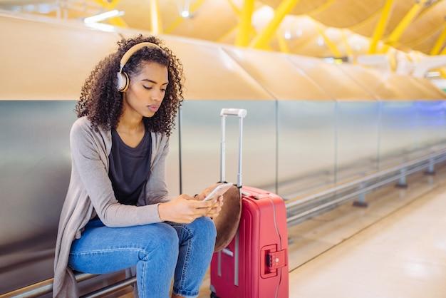 Música jovem feliz com fones de ouvido e telefone celular no aeroporto