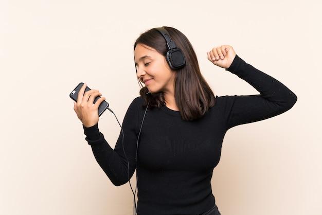 Música jovem morena com um celular sobre parede isolada