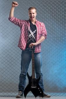 Música. jovem músico com uma guitarra na parede de cerca