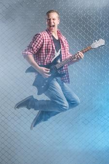 Música. jovem músico com uma guitarra no ar