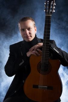Música. jovem músico em terno preto, segurando um violão