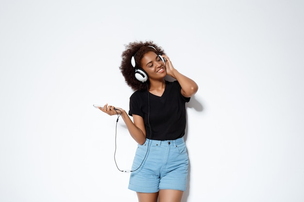 Música linda garota africana em fones de ouvido sobre parede branca.