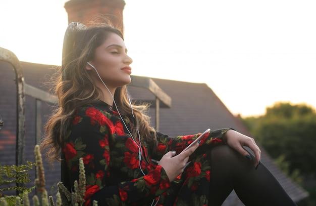 Música linda garota de seu telefone, sentado em um telhado