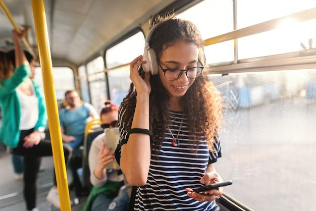 Música linda mulher de raça mista, usando telefone inteligente e transporte público em pé.