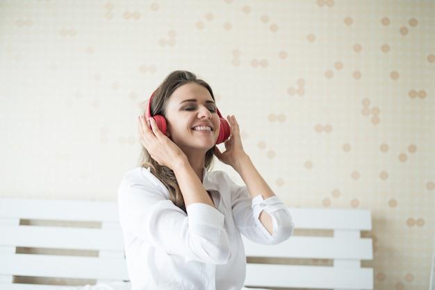 Música linda mulher na manhã sentado na cama em casa