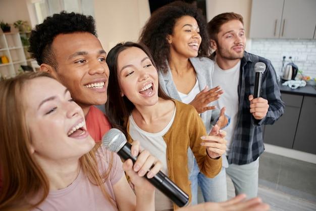 Música para a vida, amigos multiculturais felizes cantando com microfone enquanto jogam karaokê em casa