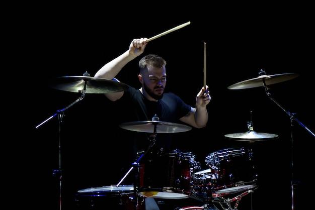Música, pessoas, instrumentos musicais e conceito de entretenimento - músico masculino com baquetas tocando bateria e pratos no concerto ou estúdio