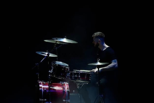 Música, pessoas, instrumentos musicais e conceito de entretenimento - músico masculino com baquetas tocando bateria no palco.