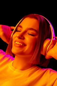 Música. retrato de uma mulher caucasiana em fundo rosa studio em luz de néon da moda. bela modelo feminino com fones de ouvido. conceito de emoções humanas, expressão facial, vendas, anúncio, moda.