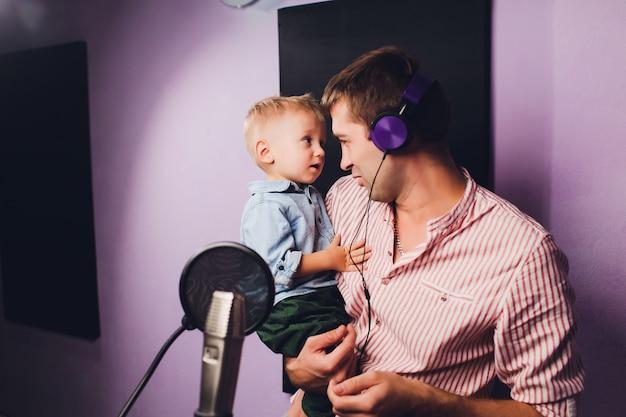 Música, show business, povos e conceito da voz - cantor masculino com fones de ouvido e música de canto do microfone no estúdio de gravação sonora.
