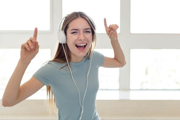 Música sorridente mulher através de fones de ouvido