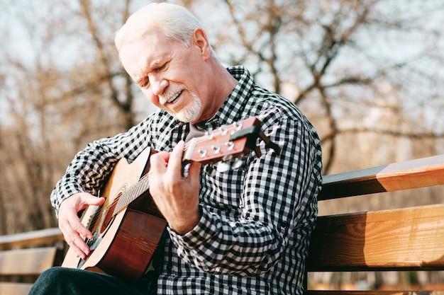 Música soul. ângulo baixo de um homem maduro em foco posando no banco e curtindo o toque de guitarra