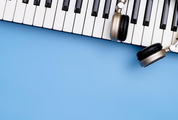 Música teclado e música de fone de ouvido no espaço da cópia azul