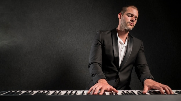 Músico apaixonado de vista frontal e seu espaço de cópia de piano digital