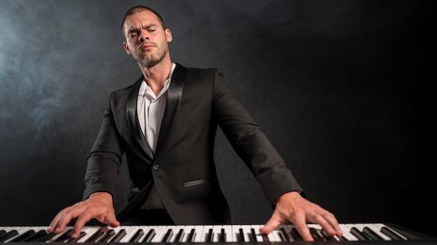Músico apaixonado tocando piano digital de frente