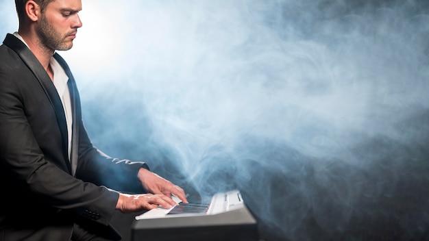 Músico artístico de vista lateral e efeito de fumaça azul