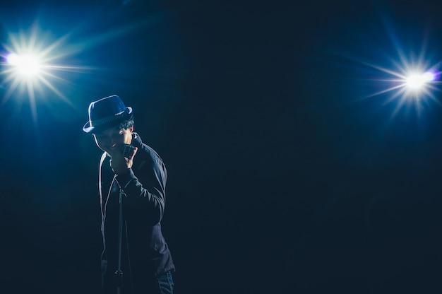 Músico asiático cantando uma canção com microfone em fundo preto com luz do ponto e reflexo de lente