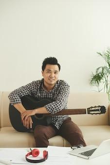 Músico asiático sorridente, sentado no sofá com guitarra em casa
