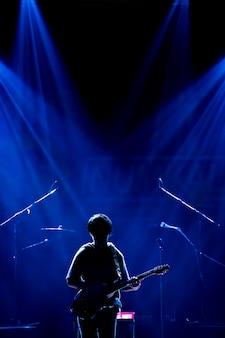 Músico asiático tocando guitarra em fundo preto com luz do ponto e reflexo de lente