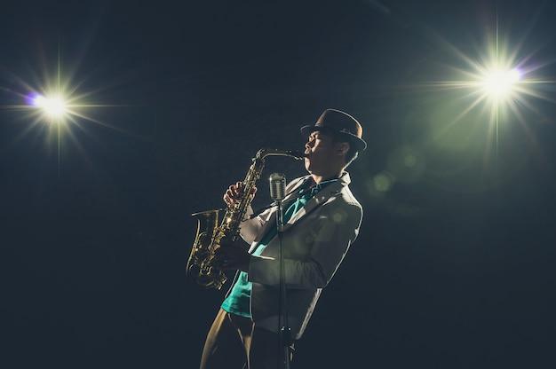 Músico asiático tocando o trompete com luz de spot e lente flare no palco, conceito musical
