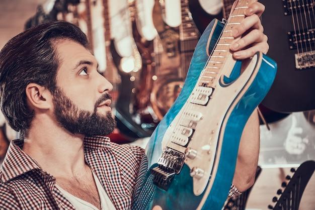 Músico barbudo escolhe guitarra elétrica na loja