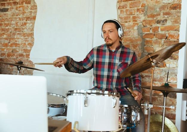 Músico caucasiano tocando bateria durante show online em casa isolado e em quarentena.