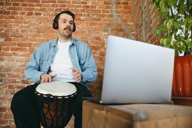 Músico caucasiano tocando tambor de mão durante show online em casa isolado e em quarentena. usando câmera, laptop, streaming, cursos de gravação. conceito de arte, suporte, música, hobby, educação.