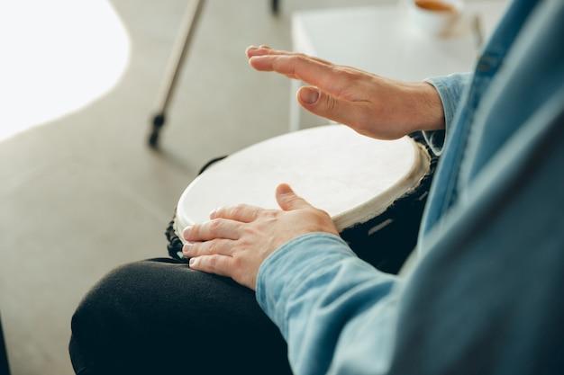 Músico caucasiano tocando tambor de mão durante show online em casa isolado e em quarentena.