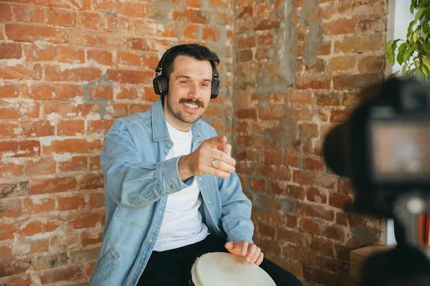 Músico caucasiano tocando tambor durante show online em casa