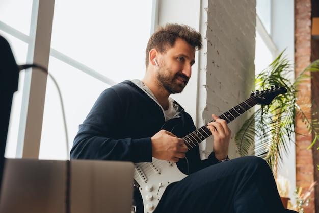 Músico caucasiano tocando violão durante concerto on-line em casa isolado e em quarentena, improvisando alegre