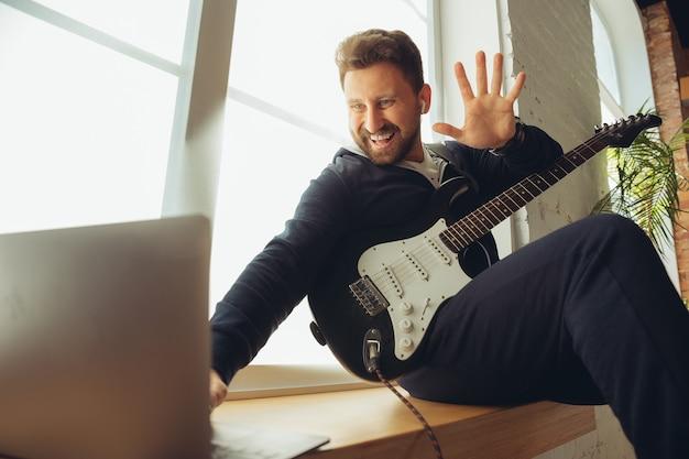 Músico caucasiano tocando violão durante show online em casa