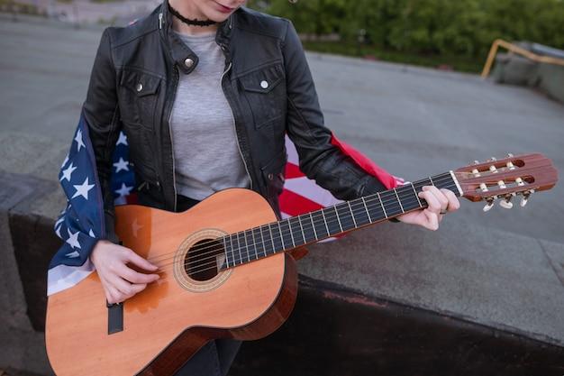 Músico com a bandeira americana tocando violão. concerto acústico no telhado. um adolescente de férias em uma festa no dia da independência