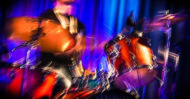 Músico com bateria. imagem abstrata de um baterista em um show. o conceito de música no coração. desfoque de movimento intencional