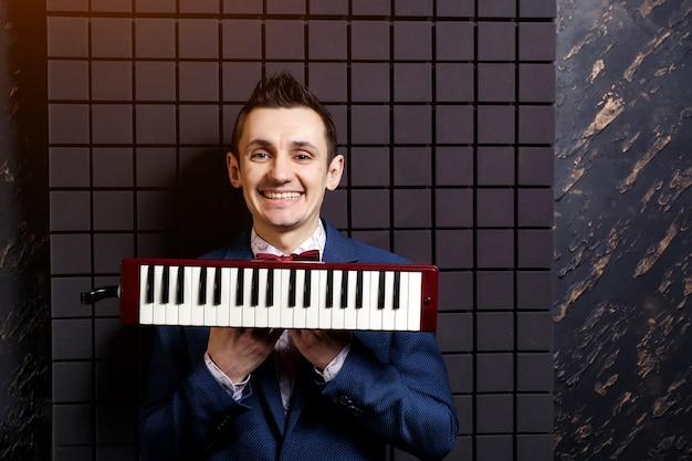 Músico com um pequeno mini piano teclado música instrumental nas mãos em um estúdio de gravação