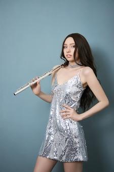 Músico com uma flauta nas mãos com roupas de palco