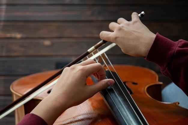 Músico com violoncelo toca cordas com as mãos