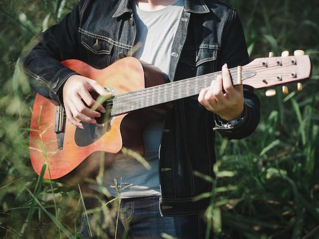 Músico considerável que joga a guitarra acústica no fundo do borrão do campo de grama.