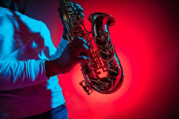 Músico de jazz afro-americano bonito tocando saxofone no estúdio em um fundo de néon. conceito de música. jovem alegre e atraente improvisando. retrato retrô do close-up.