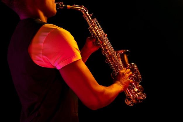 Músico de jazz tocando saxofone no estúdio em uma parede de neon