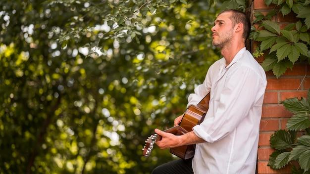 Músico de lado tocando violão ao ar livre