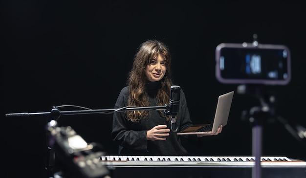 Músico de menina com laptop, gravando vídeo em smartphone em pé no tripé, usando microfone profissional, blogueiro ou curso de tiro de professor de música em estúdio, sentado ao piano.