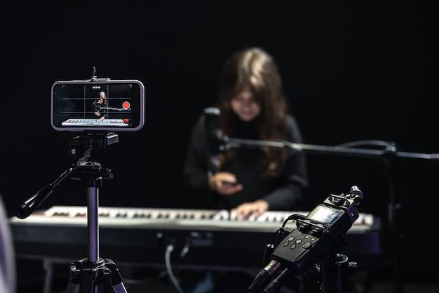 Músico de menina gravando vídeo em smartphone de pé no tripé, usando microfone profissional, blogueiro ou curso de tiro de professor de música em estúdio, sentado ao piano.