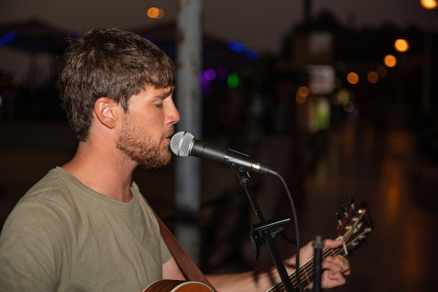 Músico de rua canta uma música e toca violão à noite. cantor concentrado atuando, ele está usando um microfone e um instrumento - conceito de entretenimento e música.