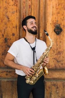 Músico de smiley com sax olhando para longe