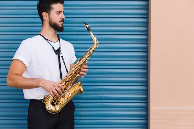Músico de tiro médio lateral posando com saxofone