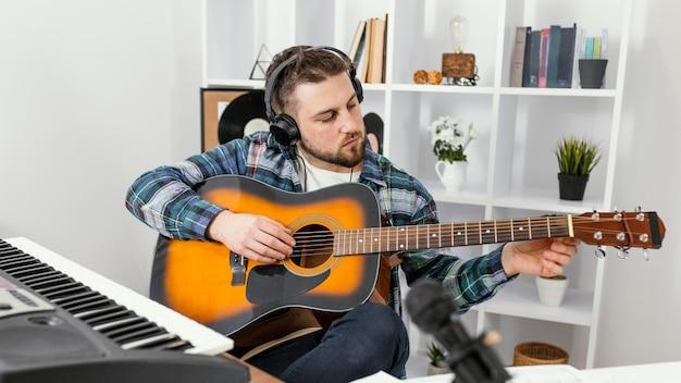 Músico de tiro médio tocando violão