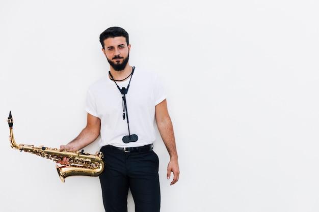 Músico de tiro médio vista frontal posando com saxofone