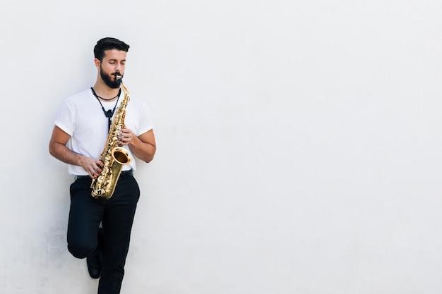 Músico de tiro médio vista frontal tocando saxofone