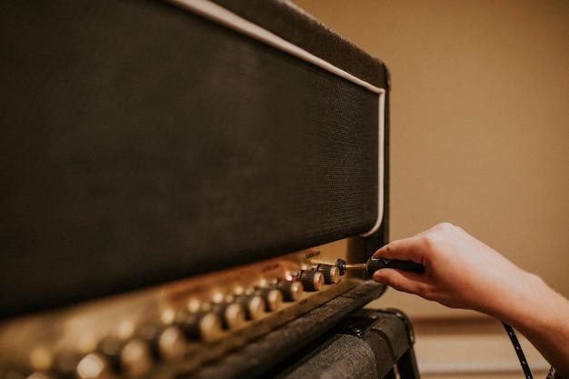 Músico definindo amplificador de guitarra, foto da sessão de gravação em estúdio