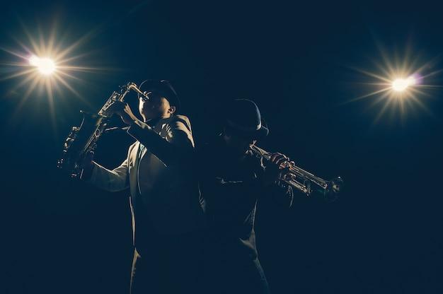 Músico duo banda tocando o trompete com luz de spot e lente flare no palco, conceito musical
